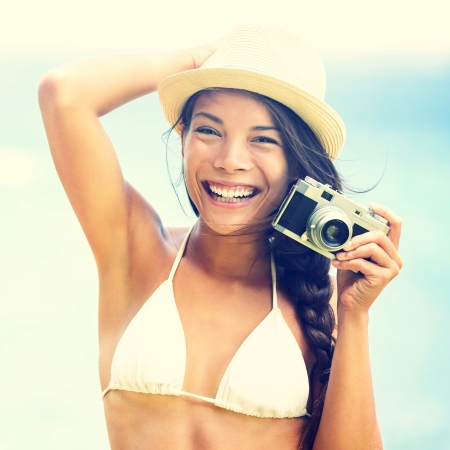 Beach woman with vintage retro camera having fun playful laughing in bikini on blue ocean background wearing beach hat  Multicultural Asian   Caucasian girl  Stock Photo - 18351607