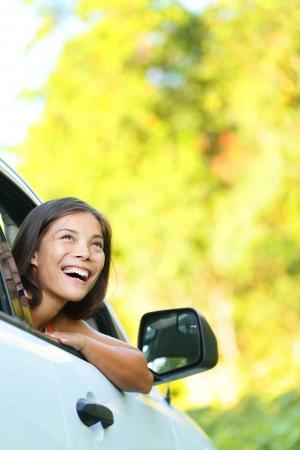 aandrijvingen: Auto vrouw op road trip die uit venster kijkt lachend blij Mooie multiculturele Aziatische blanke vrouw