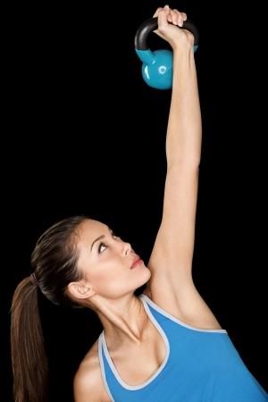 kettles: Fitness mujer con formaci�n crossfit kettlebell. Montar instructor de fitness multicultural hermoso aislado en fondo negro.