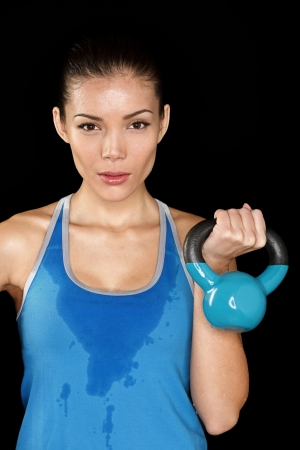 sweaty: Fitness exercise crossfit woman holding kettlebell strength training biceps. Beautiful sweaty fitness instructor looking intense at camera. Mixed race Asian Caucasian female fitness model sweating isolated on black background. Stock Photo