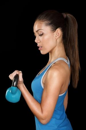 kettles: Crossfit fitness exercise Woman Holding kettlebell b�ceps entrenamiento de la fuerza. Instructor de fitness Hermosa sudoroso buscando intenso en la c�mara. Raza mixta asi�tica cauc�sica modelo femenino de la aptitud sudoraci�n aislado en fondo negro.