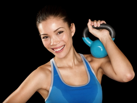 Fitness cross fit woman holding kettlebell. Portrait of training fitness instructor fitness model woman isolated on black background. Beautiful multicultural Asian Caucasian girl smiling happy, healthy and fresh. photo