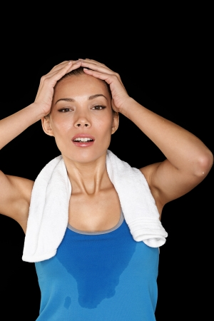 Fitness woman sweating. Beautiful sport girl with towel and sweat looking at camera tired, exhausted and sweaty after gym exercise. Multiracial Caucasian  Chinese Asian fit female fitness model isolated on black background. Stock Photo