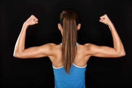 krachtige vrouw: Sterke fitness vrouw toont rug en biceps spieren sterkte. Geschikt meisje fitness model op een zwarte achtergrond.