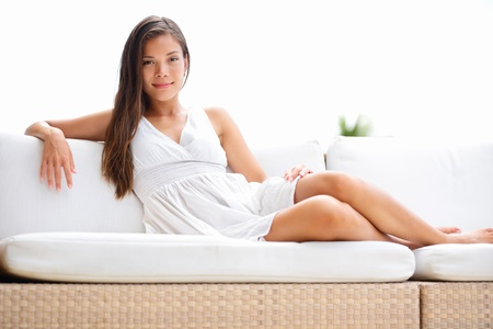 attractive couch: Woman luxury living lifestyle lying on sofa outside smiling confident