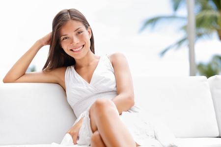 magabiztos: Portré fiatal boldog magabiztos ázsiai nő ül kint a kanapén, mosolygós