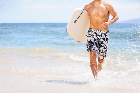 surfers: Beach fun surfer man running with bodyboard. Fit fitness model doing water sport bodyboarding surfing Stock Photo