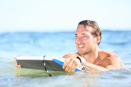 bodyboarding: Beach fun - man bodyboarding on bodyboard smiling happy surfing on boogieboard during holidays beach travel