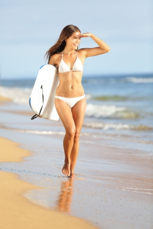 surfers: Beach fun woman surfing with bodyboard on summer vacation holidays travel