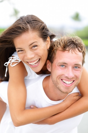 Couple happy having fun piggybacking and laughing outdoors during summer holidays travel vacation Stock Photo - 18731069