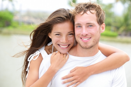 interracial relationships: Young couple smiling happy portrait outdoors. Interracial couple in love together outside looking fresh and joyful at camera. Asian woman, Caucasian man. Stock Photo