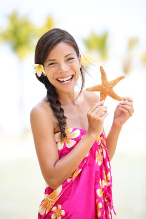 Summer vacation woman smiling happy holding starfish on Hawaiian beach. Cute multicultural Asian Caucasian female model joyful and adorable in red pink sarong photo