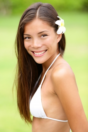 Bikini girl wearing Hawaiian flower in hair. Young woman smiling fresh and healthy. Gorgeous mixed race Asian Caucasian female model on Hawaii. photo
