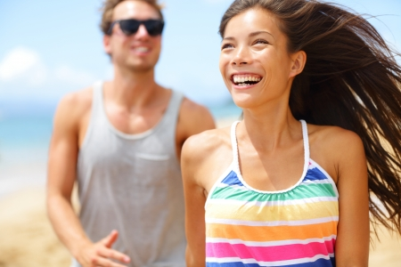 couple laughing: Young happy couple laughing having fun on beach. couple holding hands running playful and cheerful smiling happy on beach outside during summer vacation. Asian woman, Caucasian man.