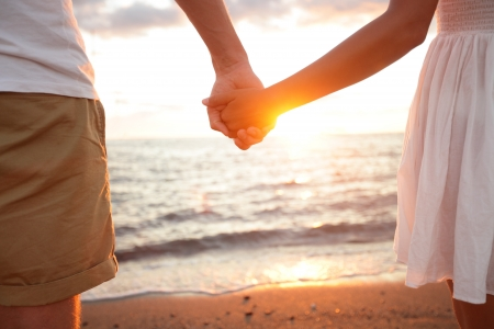 couple holding hands: Summer couple holding hands at sunset on beach. Romantic young couple enjoying sun, sunshine, romance and love by the sea. Couple on summer vacation travel holiday.