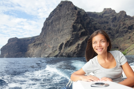 Woman on boat sailing looking at ocean smiling happy and free photo