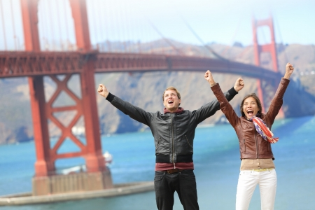 San Francisco happy people tourist couple at Golden Gate Bridge. Young attractive modern couple cheering happy, excited and joyful. California tourism concept with cheerful tourists. Stock Photo