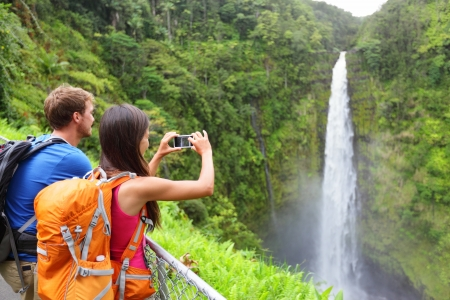 taking picture: Couple tourists on Hawaii by waterfall taking photo pictures