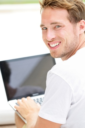 looking at computer screen: Laptop man smiling happy using computer pc outside. Young white joyful caucasian model lifestyle image. Stock Photo