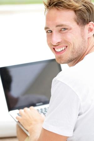 computer model: Laptop man smiling happy using computer pc outside. Young white joyful caucasian model lifestyle image. Stock Photo
