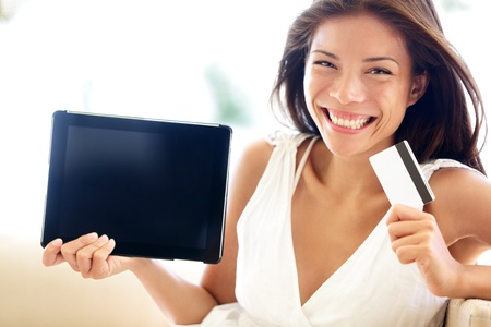 Internet shopping woman online with tablet pc and credit card. Internet shopper buying things on the internet showing blank tablet pc computer as sign. Multicultural Asian Caucasian model smiling happy photo