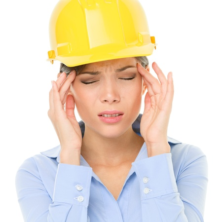 Engineer or architect woman worker having headache migraine stress wearing yellow hard hat photo