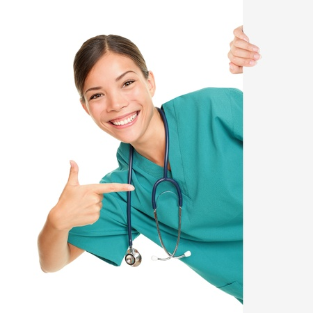nurses: Medical sign person - woman showing blank poster billboard placard pointing. Young female nurse or medical doctor professional in green scrubs smiling happy isolated on white background.