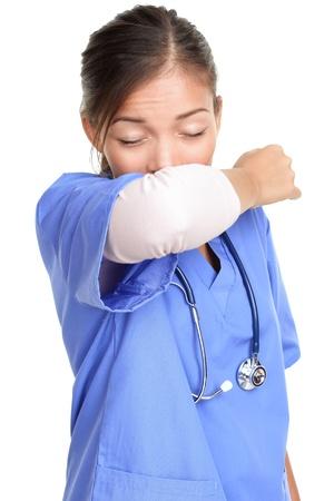 elleboog: Niezen vrouw medisch verpleegkundige of arts die elleboog niezen ziek zijn met de koude griep. Niezen instructie concept met persoon in de medische scrubs. Jonge vrouwelijke geïsoleerd op witte achtergrond