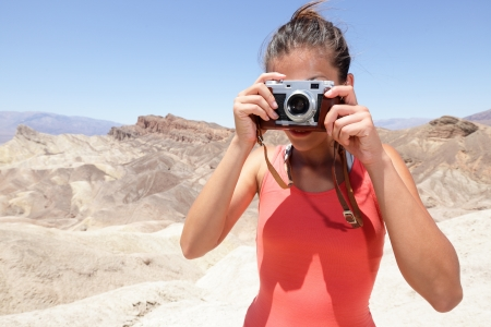 Tourist photographer woman taking pictures photo in Death Valley desert landscape of Zabriskie Point in Death Valley National Park, California, USA. Young woman on travel in United States. photo