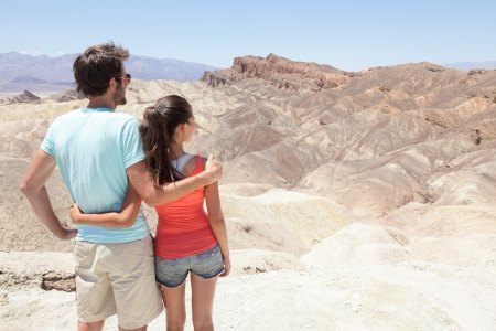 Death Valley tourists people in California enjoying view\ desert landscape of Zabriskie Point in Death Valley National Park,\ California, USA. Young couple on travel road trip in United\ States.