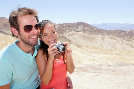 Tourists couple fun in Death Valley. Tourist woman and man taking pictures with camera enjoying the view and desert landscape of Zabriskie Point in Death Valley National Park, California, USA. photo