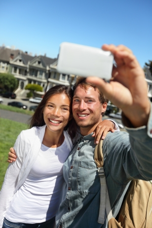 Couple fun taking self-portrait photo with cell phone camera. Multiracial happy tourist couple on travel vacation in San Francisco, Alamo Square, USA. Stock Photo - 18906227