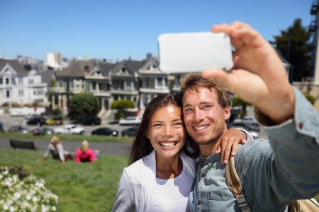 Happy young couple in San Francisco Alamo Square taking self-portrait photo pictures with smart cell phone camera. Multiethnic interracial couple tourists on sightseeing travel in California, USA photo