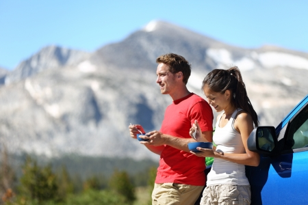 scenic drive: Couple on car road trip travel eating lunch break outdoors smiling happy. Multiracial couple, Asian woman, Caucasian man People in Yosemite National Park, California, United States. Stock Photo