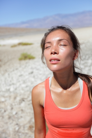 exhaustion: Thirst - dehydrated thirsty woman sweating in Death Valley desert, USA. Woman suffering from dehydration and exhaustion. Stock Photo