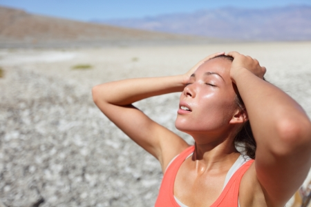 Desert woman thirsty dehydrated in Death Valley. Dehydration, overheating, thirst and heat stroke concept image with girl in desert nature. photo