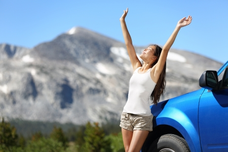 national holiday: Summer car travel freedom woman in Yosemite National Park with arms raised up cheerful and happy. Summer road trip traveler concept from Yosemite National Park, California, USA.