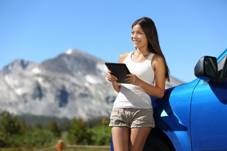 roadtrip: Traveler woman using tablet on Yosemite National Park car road trip vacation travel. Young woman reading guide book map on tablet computer pc relaxing on car with mountain landscape in background. Stock Photo