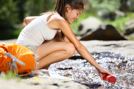 woman hiking: Hiker woman taking water in river in Yosemite National Park after hiking  Happy girl smiling enjoying outdoors summer trekking vacation  Multicultural woman in California, USA  Stock Photo
