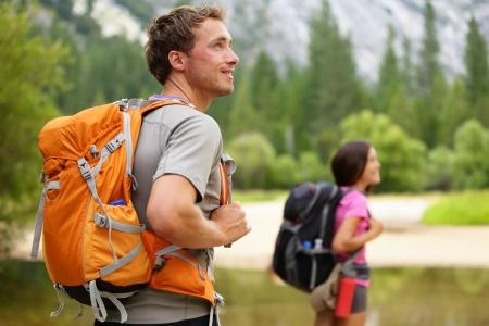 mochila viaje: Senderista - gente caminar, el hombre busca en la naturaleza paisaje de monta�a esc�nica con la mujer en el fondo Feliz pareja multicultural en el Parque Nacional Yosemite, California, EE.UU.