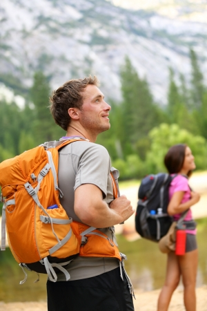 Travel Backpack: Gente Senderismo - excursionista hombre mirando a la naturaleza del paisaje con monta�as y una mujer en el fondo Feliz pareja joven multirracial caminatas al aire libre en el Parque Nacional Yosemite, California, Estados Unidos Foto de archivo