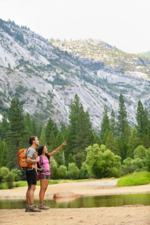 Hiking people on hike in mountains in Yosemite  Hikers young couple pointing looking up in mountain landscape in Yosemite National Park, California, USA  Multicultural couple active outdoors  photo