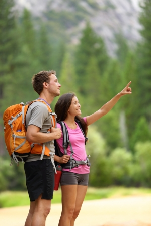 Hiking people  A couple of hikers pointing looking at nature in beautiful landscape mountains of Yosemite National Park, California, USA  Young multiracial couple on hike, Caucasian man, Asian woman
