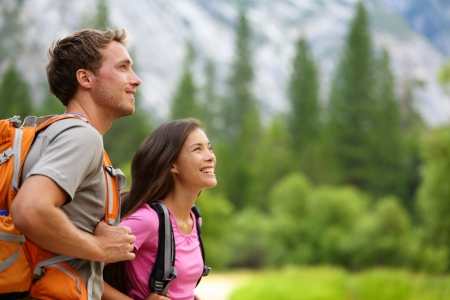 yosemite: Couple - active hikers hiking enjoying view looking at mountain forest landscape in Yosemite National Park, California, USA  Happy multiracial outdoors couple, young Asian woman and Caucasian man