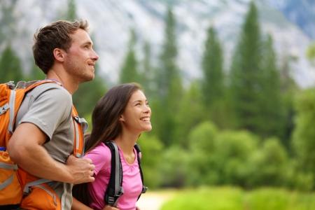 Paar - actieve wandelaars wandeling genieten van uitzicht kijken berg boslandschap in Yosemite National Park, California, USA Gelukkig multiraciale buitenshuis paar, jonge Aziatische vrouw en blanke man Stockfoto