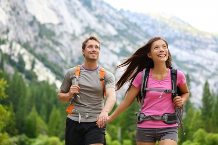 Happy couple of hikers hiking holding hands joyful, cheerful and fresh  Young active multiracial couple in outdoor activity hike in Yosemite National Park, California, USA  Asian woman, Caucasian man