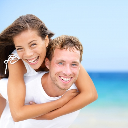 perfect teeth: Happy couple on beach fun summer vacation  Multiracial Young newlywed couple piggybacking smiling joyful elated in happiness concept on tropical beach with blue water, sky  Asian woman, Caucasian man  Stock Photo