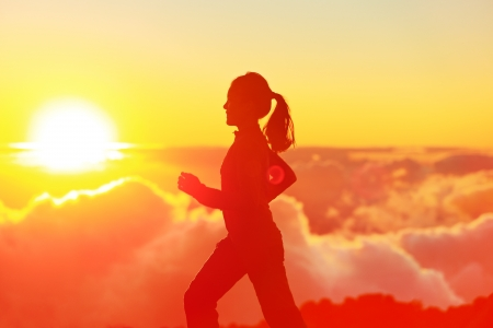 light trails: Runner woman running in sunshine sunset  Fitness athlete training trail running marathon in mountains above the clouds in beautiful mountain landscape  Female in jogging in silhouette