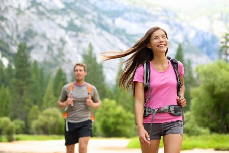 yosemite: People hiking - happy hikers on hike trekking travel trek during summer vacations outdoors in beautiful forest mountain landscape in Yosemite national park, California, USA. Man and woman together.