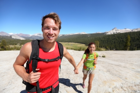 yosemite: Hiking couple having fun outdoors holding hands during hike. Happy outdoors activity lifestyle image with young interracial couple hikers. From Pothole Dome, Yosemite National Park, California, USA. Stock Photo